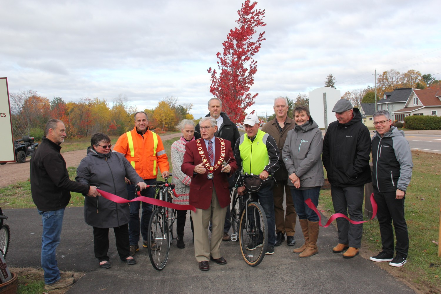 Official ribbon cutting in October, 2019 marked the opening of a twinned section of the Algonquin Trail through the urban commercial core of the Town of Petawawa. Members from the various groups involved in the trail attended. In the photo from left, Mark Reinert, Petawawa parks and recreation facilities supervisor, Sheila Clarke, Petawawa Accessibility Advisory Committee member, David Unrau (Petawawa public works director), Laura Lapinskie, constituency assistant to MPP John Yakabuski, Petawawa Mayor Bob Sweet, Jason Davis, manager of forestry and GIS services with Renfrew County, Ron Moss, Ottawa Valley Cycling and Active Transportation Alliance (OVCATA) secretary, Petawawa Councillor James Carmody, Dana Lawson, Garrison Petawawa Personnel Support Programs (PSP) health promotion manager, Kelly Williams, Petawawa community services director, and Petawawa CAO/clerk Dan Scissons. Photo by Anthony Dixon, Pembroke Observer, with permission.